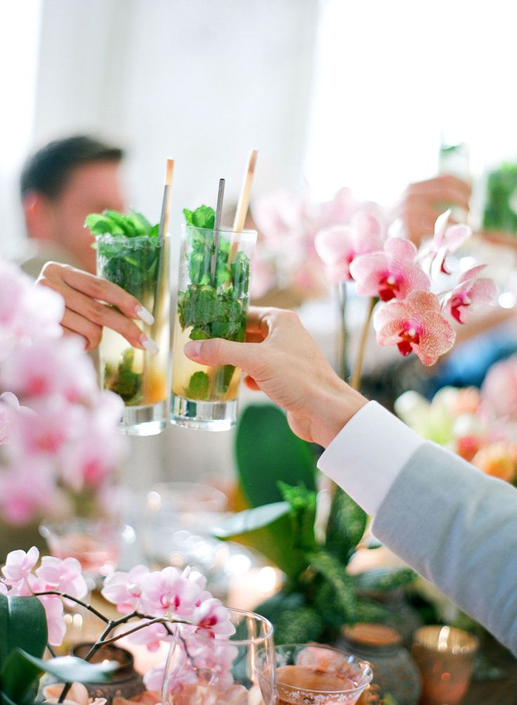guests toasting with mint cocktails, ink orchids in backdrop