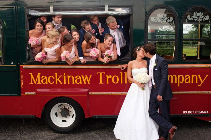 bridal party in trolly looking at bride and groom kissing