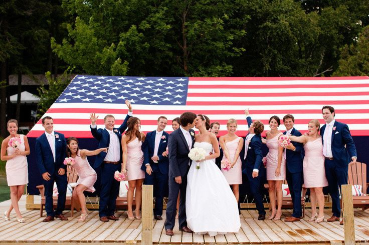 bridal party on dock with huge american flag in backdrop