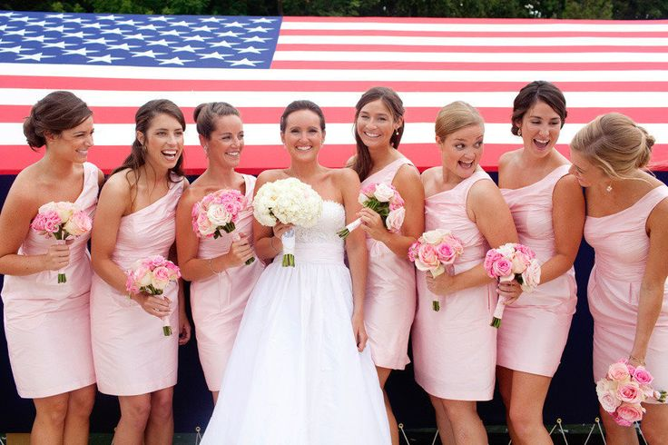 bride with bridesmaids in pink short dress against American Flag backdrop
