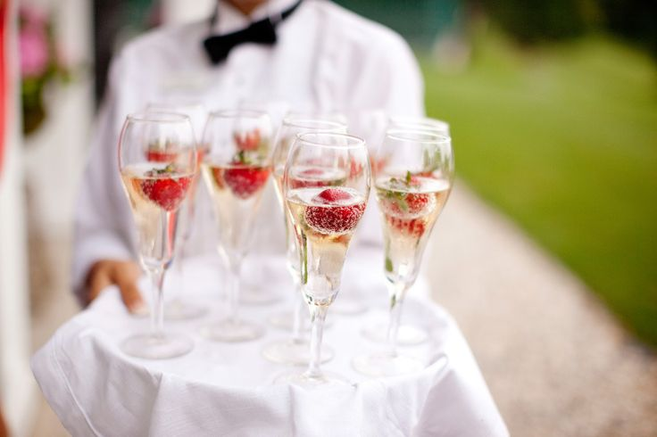 server carrying champagne with strawberries
