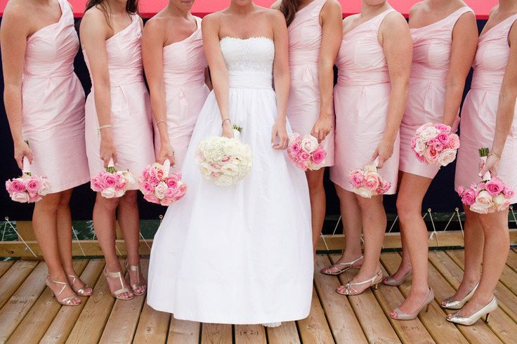 bride in oscar de la renta in the middle of bridesmaids in pink one shoulder dresses and gold heels
