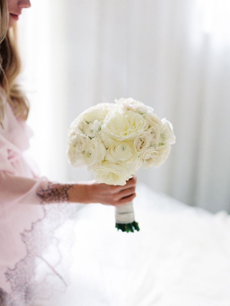 bride holding white roses in pink robe