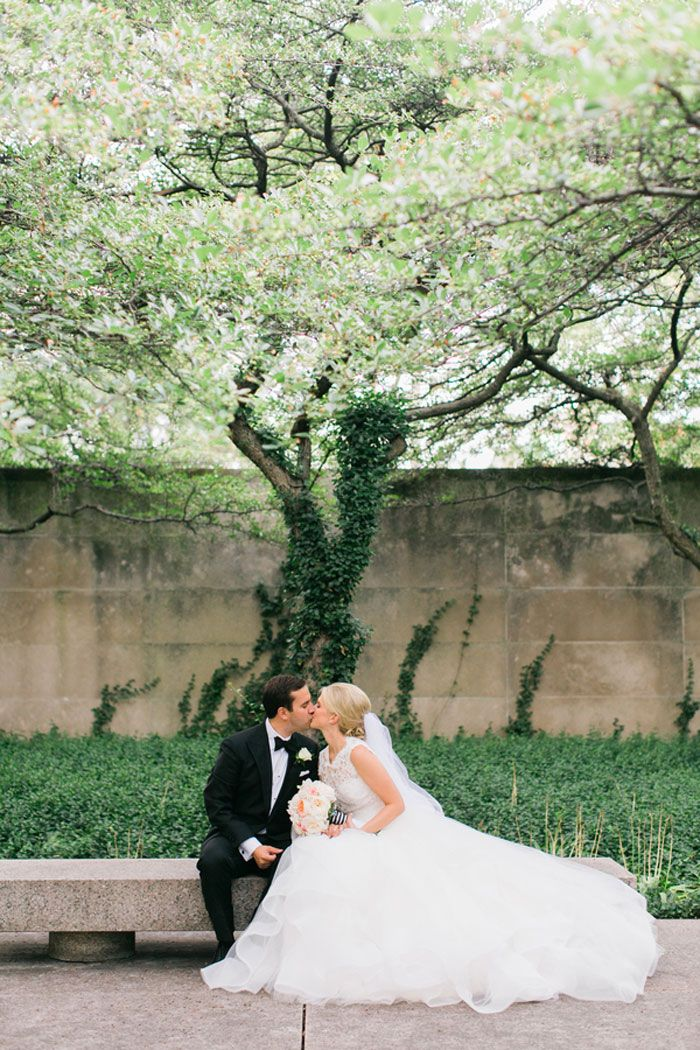 bride and groom kissing outside on a bench