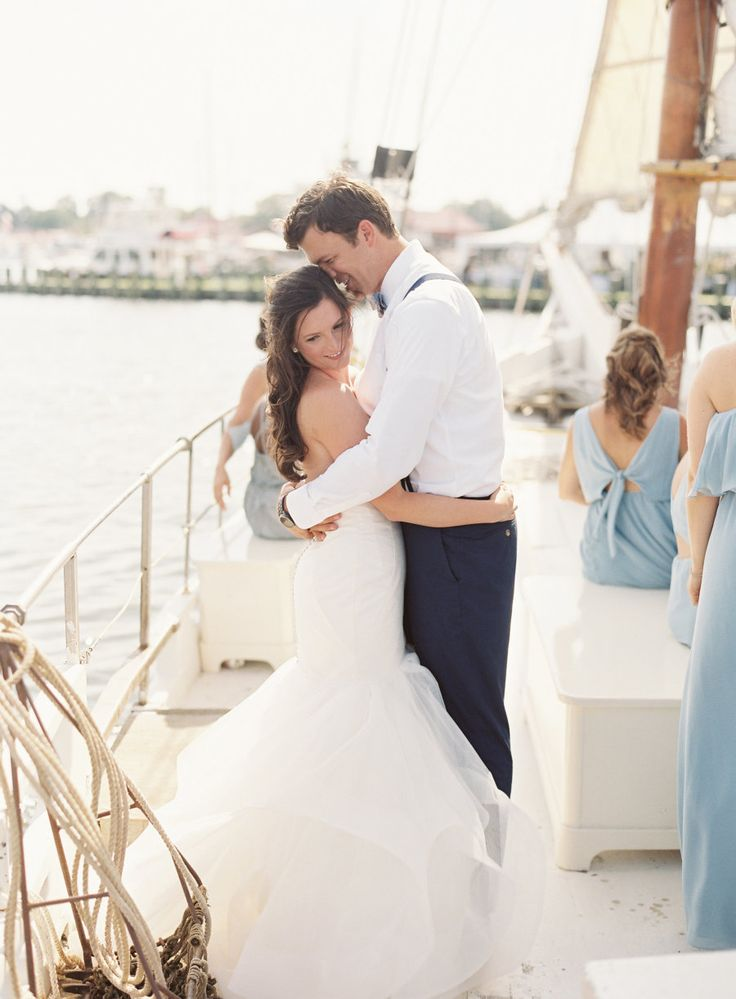bride and groom hugging on a sailboat