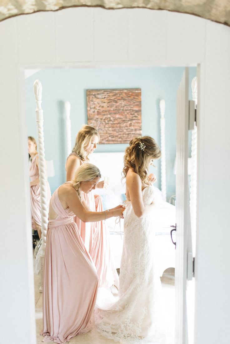 bridesmaids in pink dresses helping bride with her dress