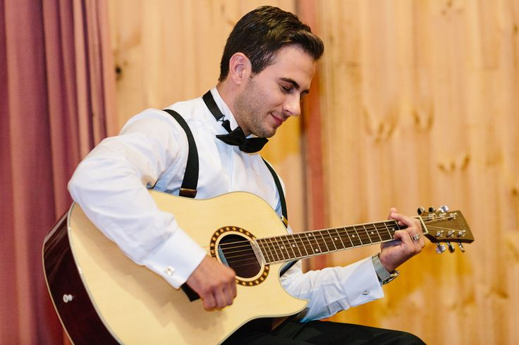 groom playing song on guitar for bride
