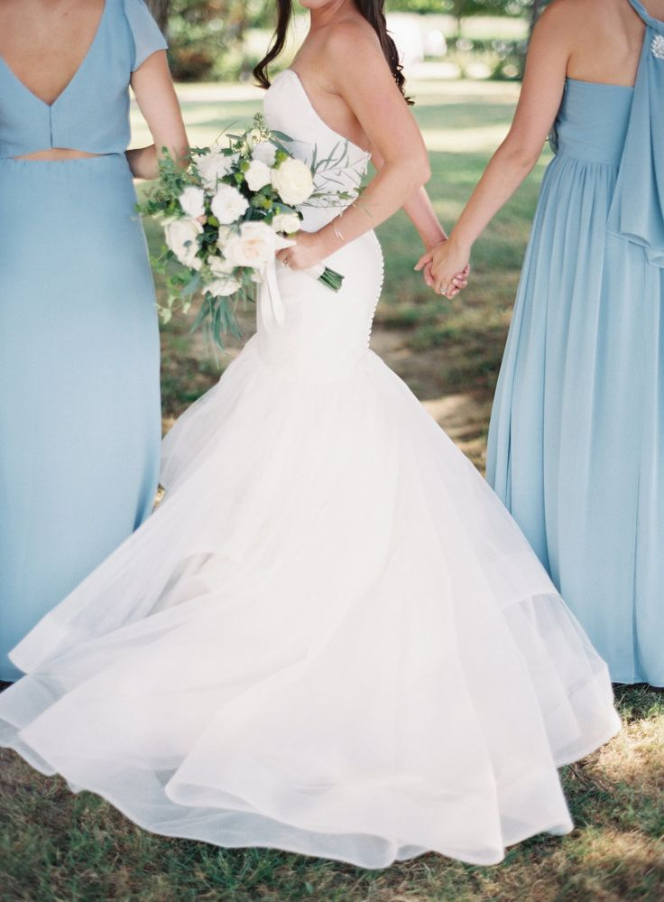 bride holding hands with bridesmaids