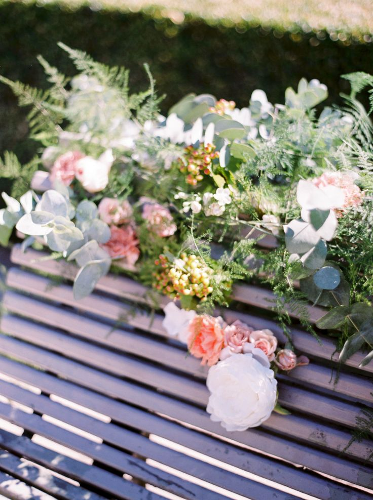 flowers peeping through park bench