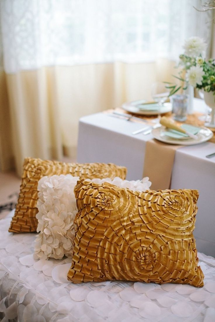 gold pillows at wedding reception table