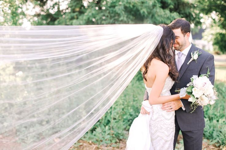 bride and groom kiss with veil blowing in the wind