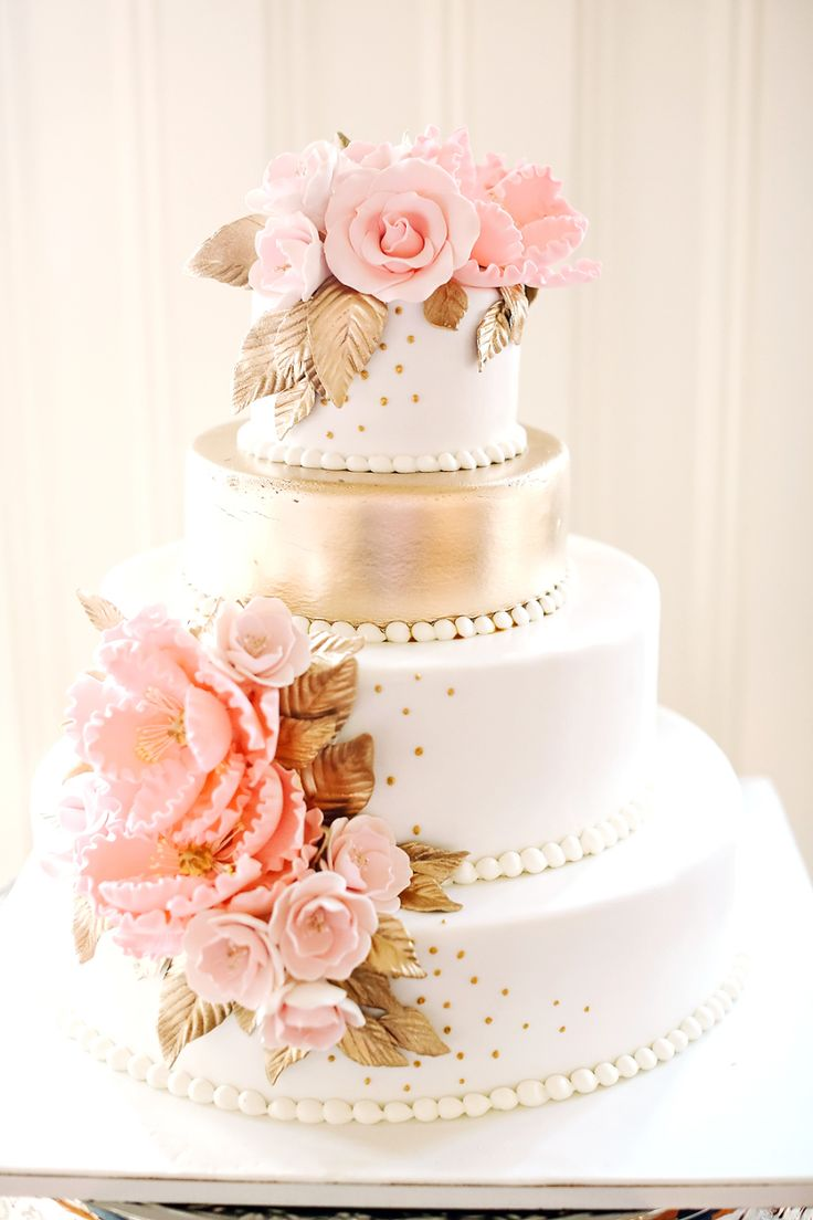 pink and gold wedding cake with pink flowers in frosting