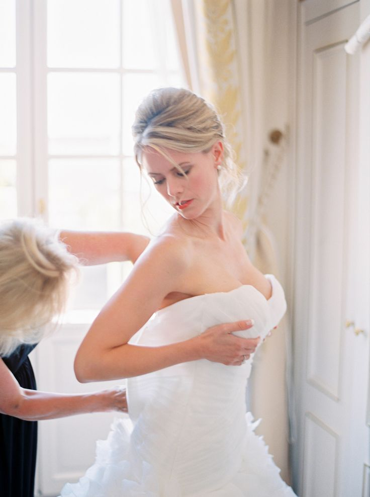 bride putting on strapless wedding dress