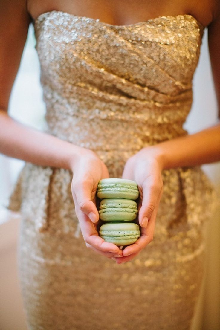 bridesmaid in gold dress holding mint macaroons