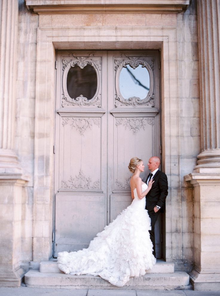 bride and groom in front of historic Paris building