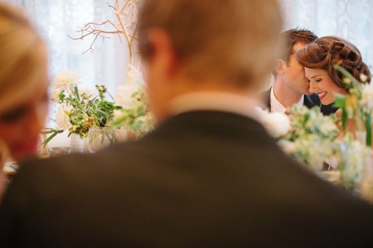 groom whispering into bride's ear