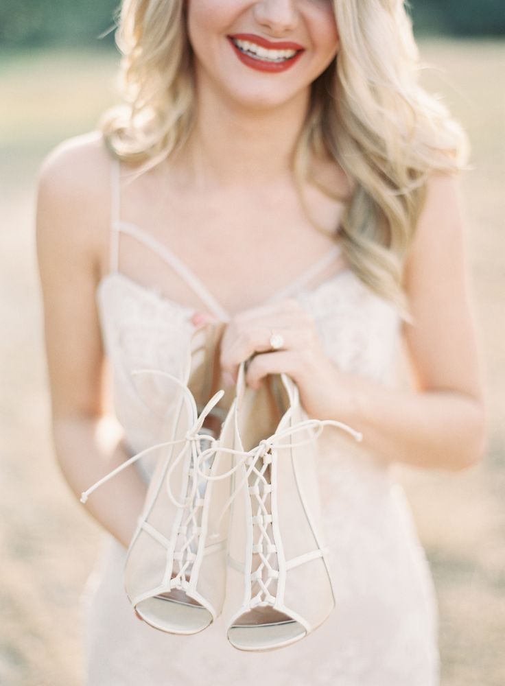 bride holding lace up wedding shoes