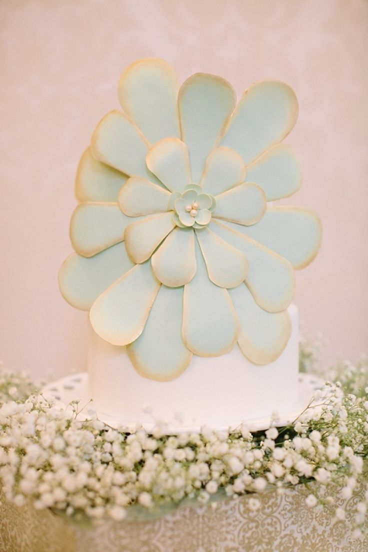 white wedding cake with baby's breath and large mint flower