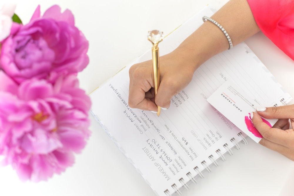 bride-to-be writing in wedding planner with gold pen with a diamond