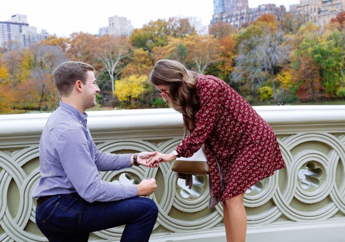guy on one knee proposing on bow bridge in Central Park
