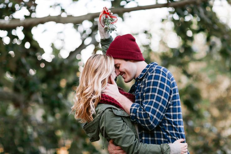 couple holding mistletoe over their heads as they kiss