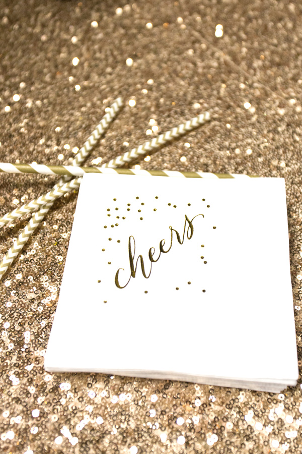 gold sequin table linens with striped straws and cheers napkins