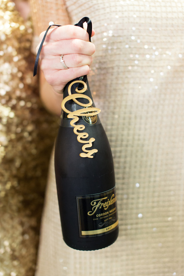 girl holding black champagne bottle
