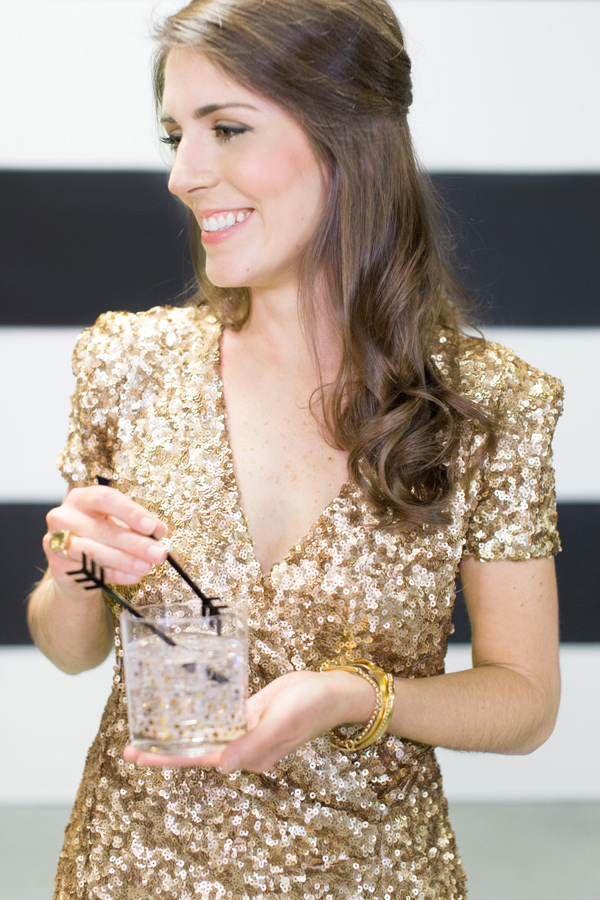 girl in gold dress holding cocktail