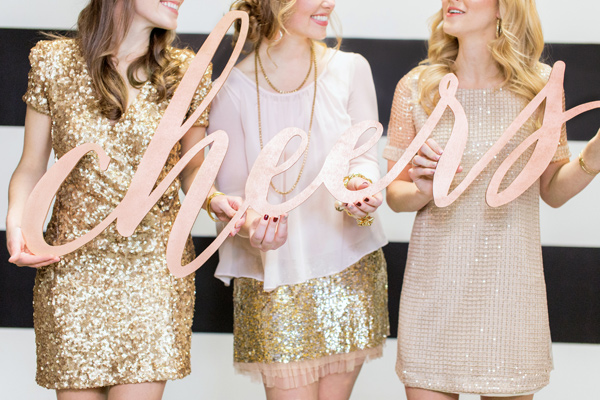 NYE party girls holding cheers sign