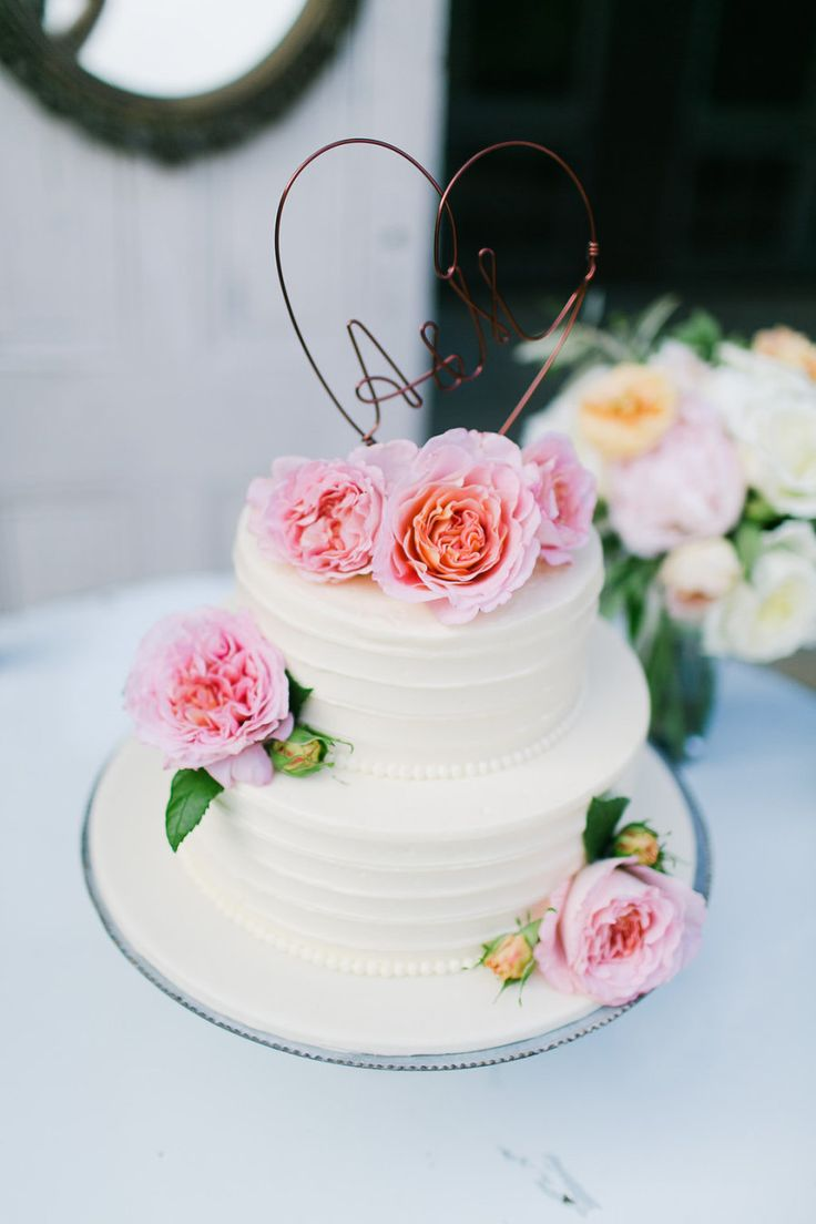 white wedding cake with pink peonies and wire heart topper