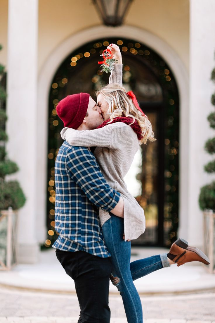 couple kissing under mistletoe during engagement session