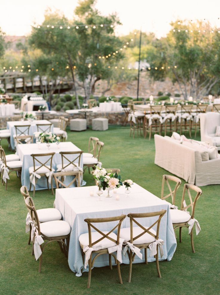 wedding rentals with square tables, powder blue linens, hanging lights and outdoor wedding rentals