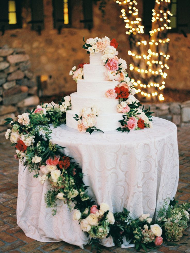 wedding cake with greenery cascading down the table with roses