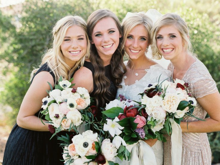 bridesmaids with bride hold mixture of flowers and wearing mix-matched bridesmaid dresses