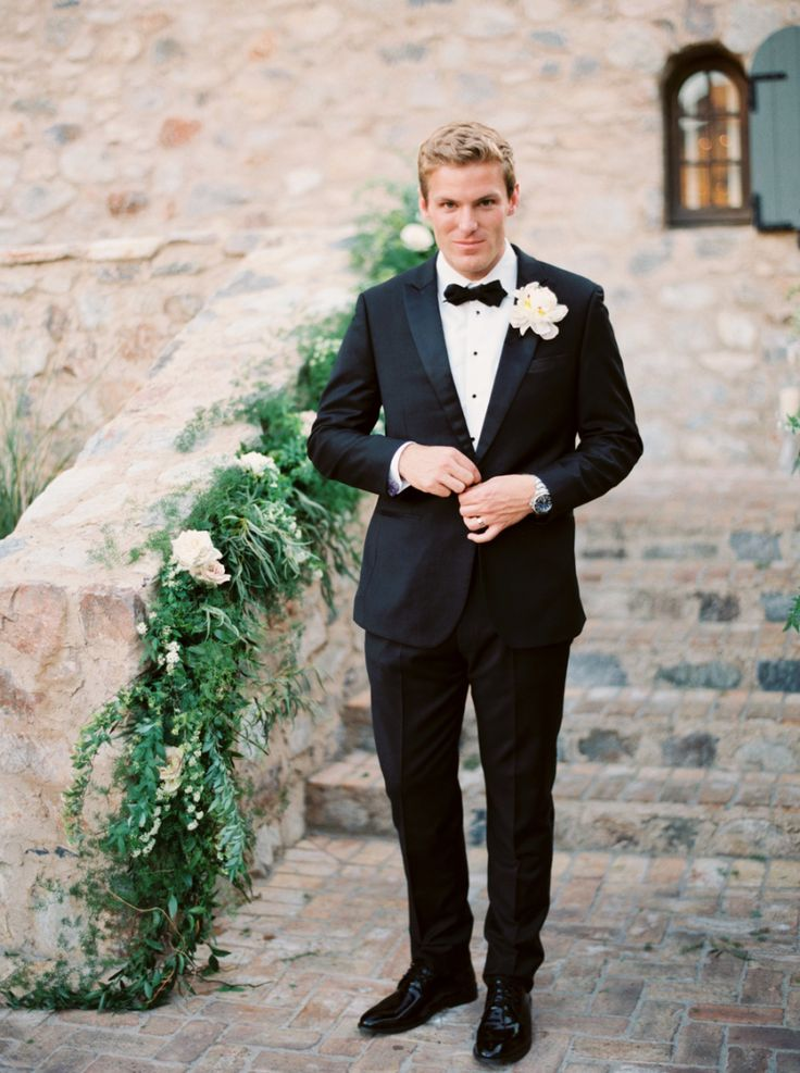 groom in black tux, and greenery wedding decor on stair railing