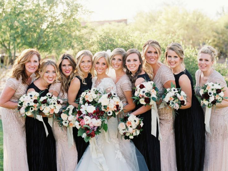 mix-matched bridesmaid dresses wearing black long dresses and gold long dresses