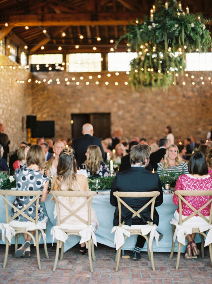 wedding guests at long kings tables with blue linens