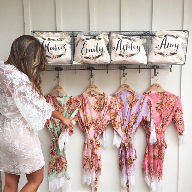 bride holding bridesmaids robes