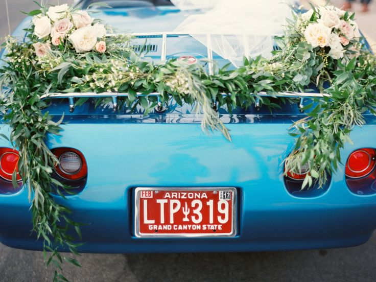 blue vintage wedding getaway car decorated with greenery and roses