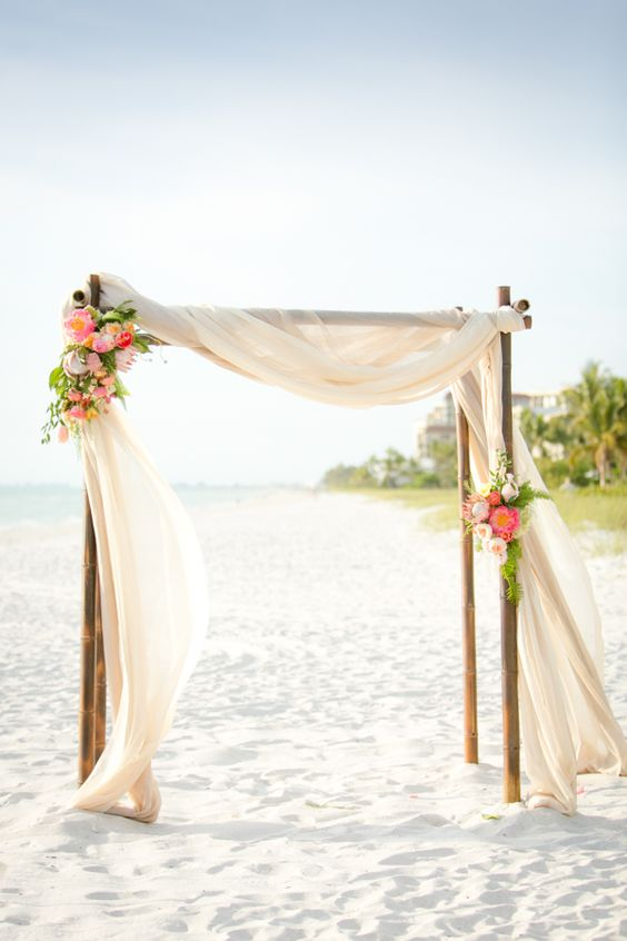 pink flowers on wedding arbor on the beach with flowing curtains