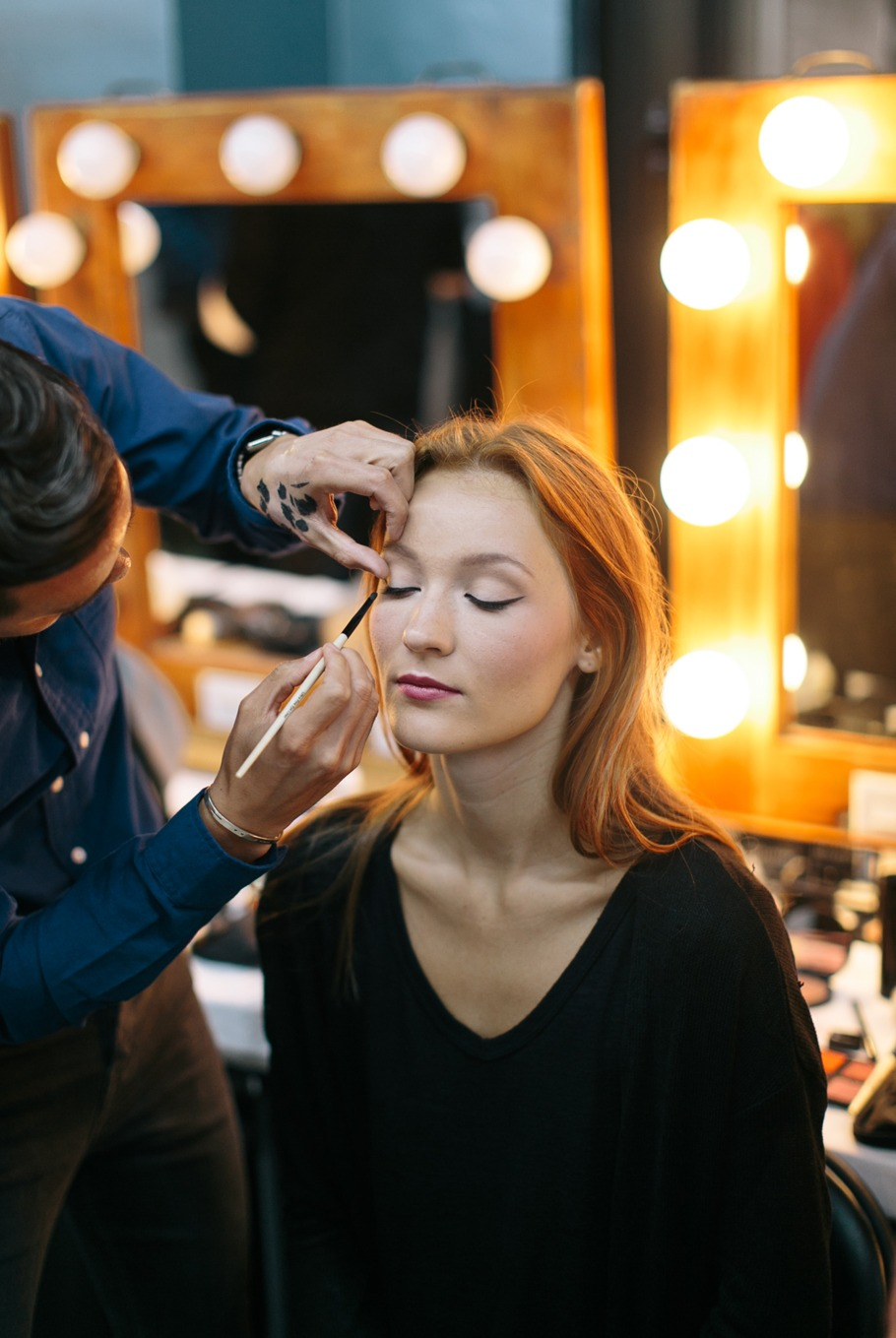model getting her makeup done for bridal fashion show