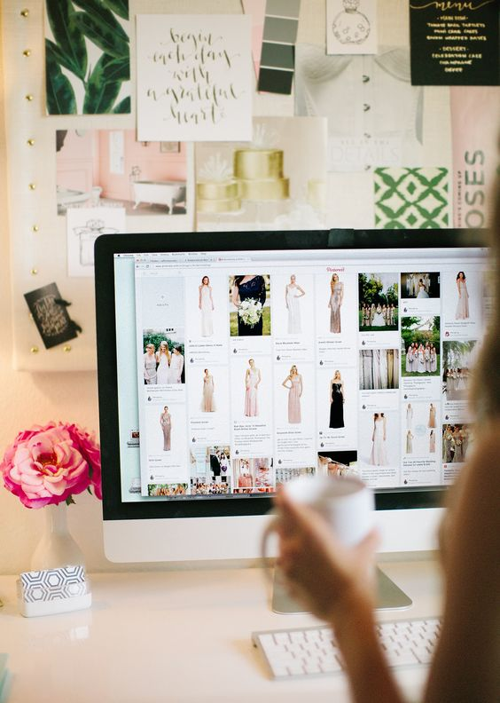 girl planning her wedding and pinning pictures to her wedding boards on Pinterest