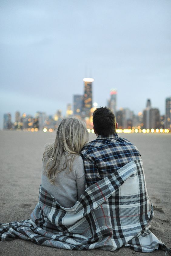 couple wrapped in a blanket overlooking chicago