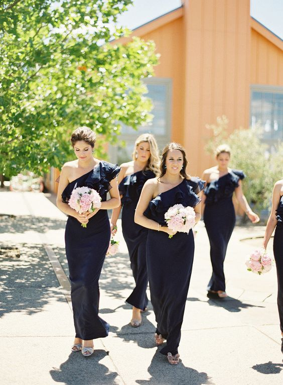bridesmaids in long off the shoulder dresses holding pink bouquets