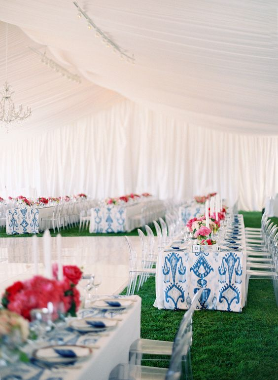 wedding reception under marquee tent with kings tables and a chandelier