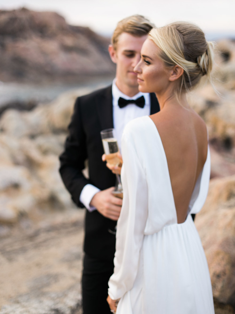 guy in tux and fiance in long white gown shooting engagement photos on rocks by the ocean