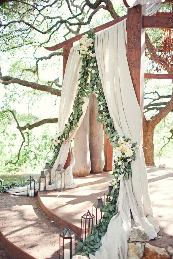 greenery lining curtains at wedding arbor