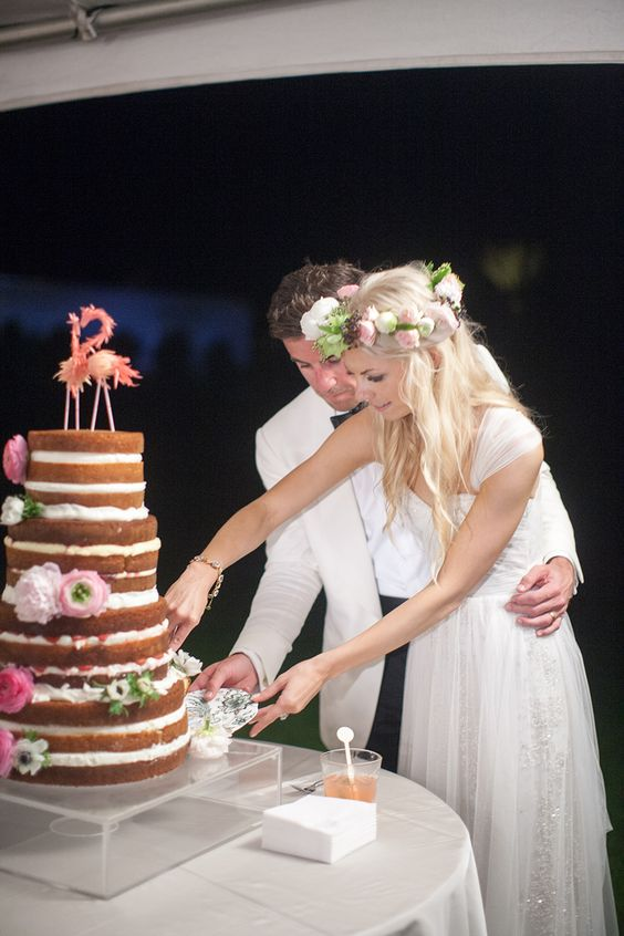 groom-assisting-bride-cutting-naked-cake-with-flamingo-cake-topper