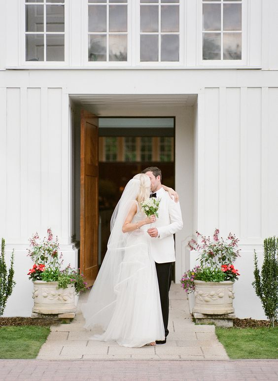 bride-and-groom-kissing-white-backdrop