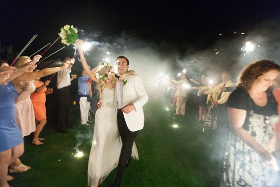 bride-in-floral-crown-and-groom-in-white-tux-walking-through-sparklers